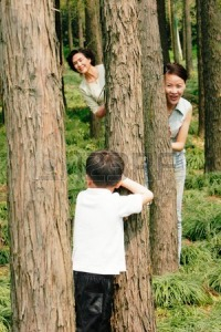 26127533-a-boy-playing-hide-and-seek-with-his-mother-and-grandmother-in-the-forest